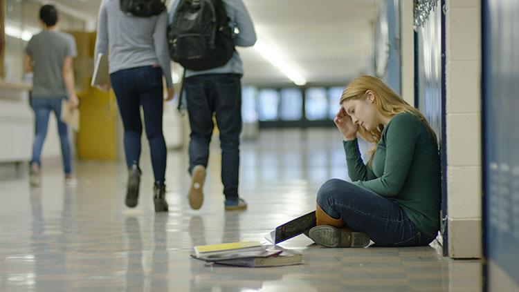 Teen sitting on floor by lockers
