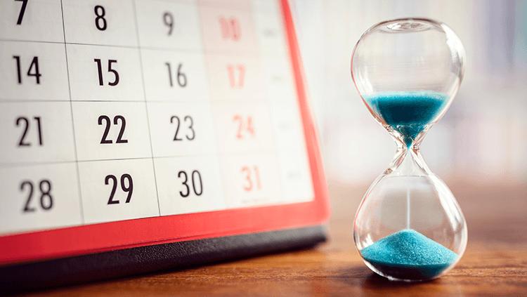 Sand hourglass next to a calendar